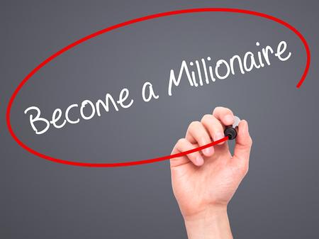 millonario: El hombre escrito a mano convertirse en un millonario con marcador negro en la pantalla visual. Aislado en gris. Negocios, la tecnología, el concepto de internet. Foto de stock