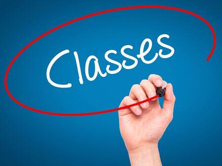 Man Hand Writing Classes avec un marqueur noir sur l'écran visuel. Isolé sur bleu Affaires, technologie, concept internet. Banque d'images