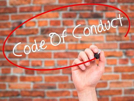 work ethic responsibilities: Man Hand writing Code Of Conduct with black marker on visual screen. Isolated on bricks. Business, technology, internet concept. Stock Photo