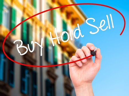 press agent: Man Hand writing  Buy Hold Sell with black marker on visual screen. Isolated on city. Business, technology, internet concept. Stock Photo