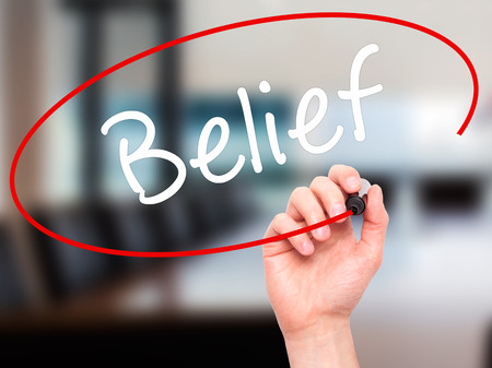 posit: Man Hand writing Belief with black marker on visual screen. Isolated on office. Business, technology, internet concept. Stock Photo