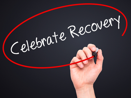recovery position: Man Hand writing Celebrate Recovery with black marker on visual screen. Isolated on black. Business, technology, internet concept. Stock Photo