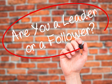 blindly: Man Hand writing Are You a Leader or a Follower? with black marker on visual screen. Isolated on bricks. Business, technology, internet concept. Stock Photo
