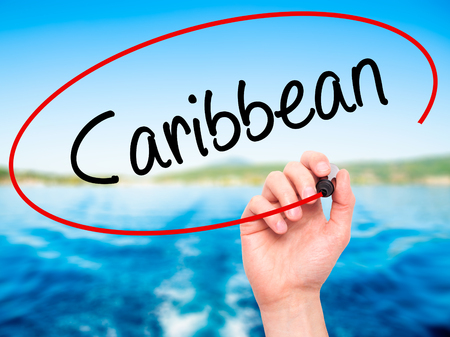 port au prince: Man Hand writing Caribbean with black marker on visual screen. Isolated on nature. Business, technology, internet concept. Stock Photo