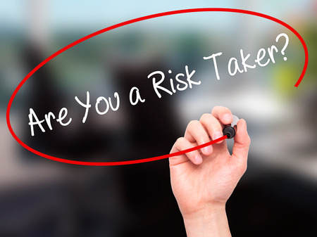 taker: Man Hand writing Are You a Risk Taker? with black marker on visual screen. Isolated on office. Business, technology, internet concept. Stock Photo