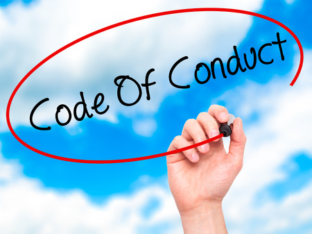 work ethic responsibilities: Man Hand writing Code Of Conduct with black marker on visual screen. Isolated on sky. Business, technology, internet concept. Stock Photo Stock Photo