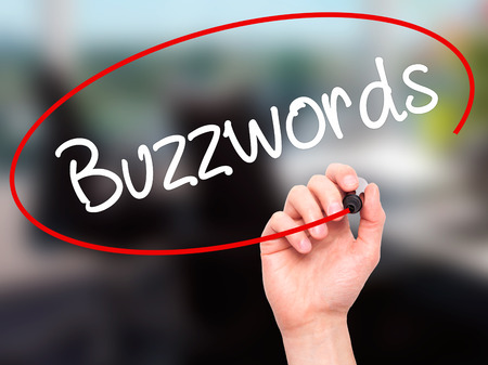 buzzwords: Man Hand writing Buzzwords with black marker on visual screen. Isolated on background. Business, technology, internet concept. Stock Photo Stock Photo