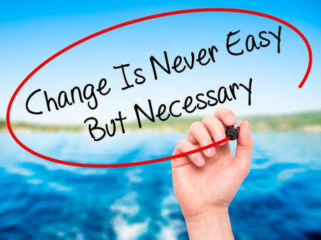 Man Hand writing Change Is Never Easy But Necessary with black marker on visual screen. Isolated on background. Business, technology, internet concept. Stock Photo