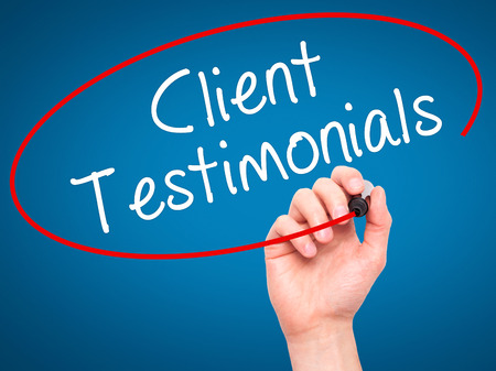 testimonials: Man Hand writing Client Testimonials with black marker on visual screen. Isolated on blue. Business, technology, internet concept. Stock Photo
