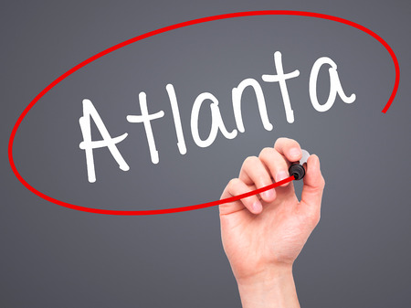 american midwest: Man Hand writing Atlanta with black marker on visual screen. Isolated on background. Business, technology, internet concept. Stock Photo