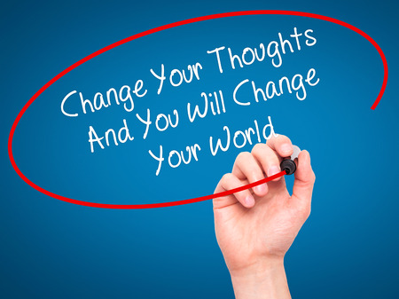 Man Hand writing Change Your Thoughts And You Will Change Your World with black marker on visual screen. Isolated on blue. Business,  internet concept. Stock Photo