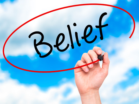 posit: Man Hand writing Belief with black marker on visual screen. Isolated on sky. Business, technology, internet concept. Stock Photo Stock Photo