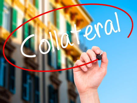 collateral: Man Hand writing Collateral with black marker on visual screen. Isolated on city. Business, technology, internet concept. Stock Photo Stock Photo