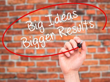 bigger: Man Hand writing Big Ideas Bigger Results  with black marker on visual screen. Isolated on city. Business, technology, internet concept. Stock Photo Stock Photo