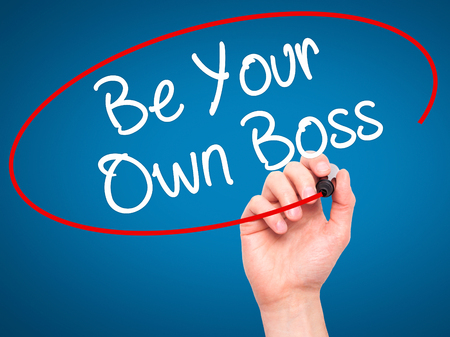 self starter: Man Hand writing Be Your Own Boss with black marker on visual screen. Isolated on blue. Business, technology, internet concept. Stock Image