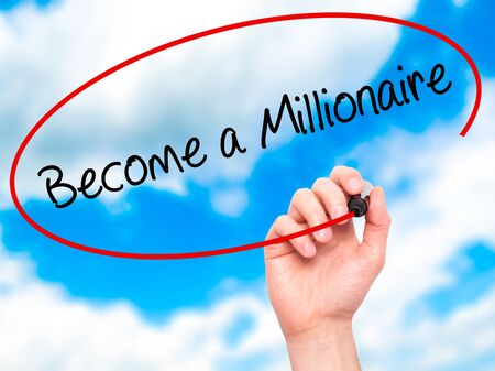 hombre millonario: Man Hand writing Become a Millionaire with black marker on visual screen. Isolated on sky. Business, technology, internet concept. Stock Photo