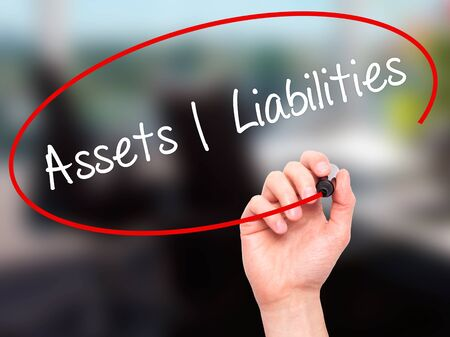 liabilities: Man Hand writing Assets Liabilities with black marker on visual screen. Isolated on office. Business, technology, internet concept. Stock Photo Stock Photo