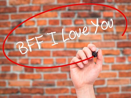 nota: Man Hand writing BFF I Love You with black marker on visual screen. Isolated on bricks. Business, technology, internet concept. Stock Photo