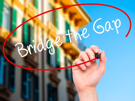 bridging the gap: Man Hand writing Bridge the Gap with black marker on visual screen. Isolated on city. Business, technology, internet concept. Stock Photo Stock Photo