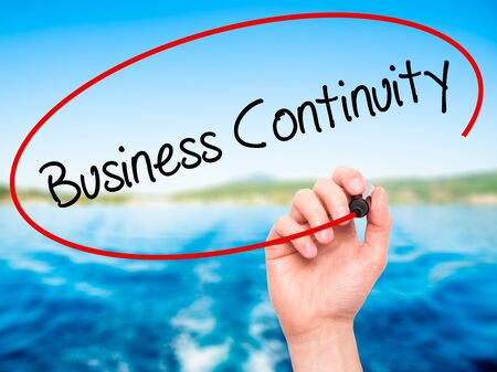 iscp: Man Hand writing Business Continuity with black marker on visual screen. Isolated on nature. Business, technology, internet concept. Stock Photo
