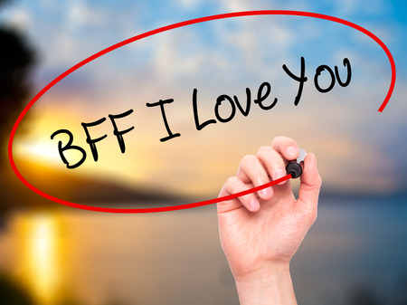 nota: Man Hand writing BFF I Love You with black marker on visual screen. Isolated on nature. Business, technology, internet concept.