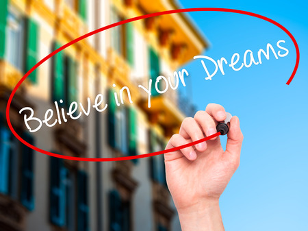 dreams of city: Man Hand writing Believe in your Dreams with black marker on visual screen. Isolated on city. Business, technology, internet concept. Stock Photo Stock Photo