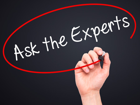 warranty questions: Man Hand writing Ask the Experts with black marker on visual screen. Isolated on black. Business, technology, internet concept. Stock Photo Stock Photo