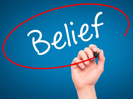 posit: Man Hand writing Belief with black marker on visual screen. Isolated on blue. Business, technology, internet concept. Stock Photo Stock Photo