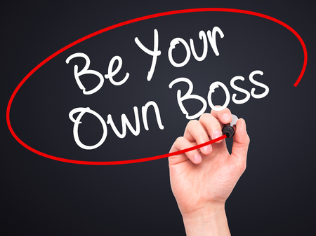 self starter: Man Hand writing Be Your Own Boss with black marker on visual screen. Isolated on black. Business, technology, internet concept. Stock Image Stock Photo