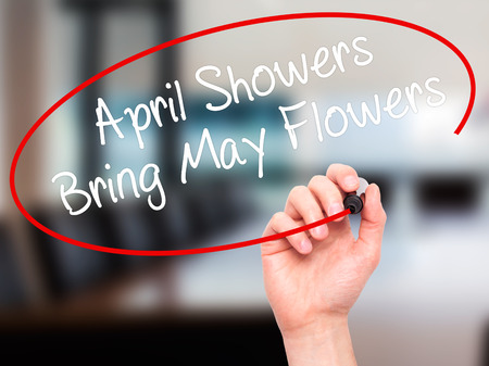 april showers: Man Hand writing April Showers Bring May Flowers with black marker on visual screen. Isolated on office. Business, technology, internet concept. Stock Photo