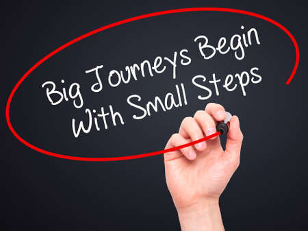 daunting: Man Hand writing Big Journeys Begin With Small Steps  with black marker on visual screen. Isolated on black. Business, technology, internet concept. Stock Photo