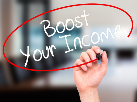 remuneration: Man Hand writing Boost Your Income with black marker on visual screen. Isolated on office. Business, technology, internet concept. Stock Photo