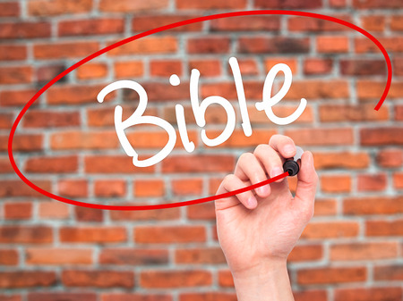 vangelo aperto: Man Hand writing Bible with black marker on visual screen. Isolated on background. Business, technology, internet concept. Stock Photo