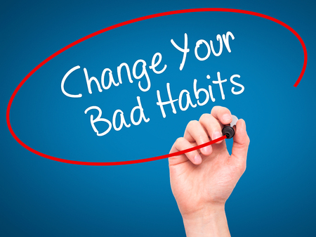 bad planning: Man Hand writing Change Your Bad Habits  with black marker on visual screen. Isolated on blue. Business, technology, internet concept. Stock Photo