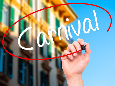 fiesta popular: Man Hand writing Carnival with black marker on visual screen. Isolated on city. Business, technology, internet concept. Stock Photo