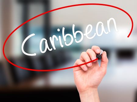 port au prince: Man Hand writing Caribbean  with black marker on visual screen. Isolated on office. Business, technology, internet concept. Stock Photo