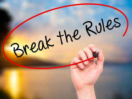 rebelling: Man Hand writing Break the Rules with black marker on visual screen. Isolated on nature. Business, technology, internet concept. Stock Photo