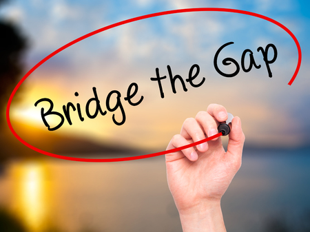 bridging the gap: Man Hand writing Bridge the Gap with black marker on visual screen. Isolated on nature. Business, technology, internet concept. Stock Photo