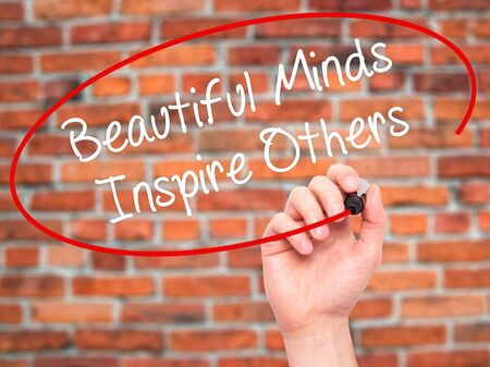 others: Man Hand writing Beautiful Minds Inspire Others with black marker on visual screen. Isolated on bricks. Business, technology, internet concept. Stock Photo
