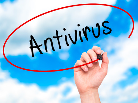 trojan horse: Man Hand writing Antivirus   with black marker on visual screen. Isolated on sky. Business, technology, internet concept. Stock Photo