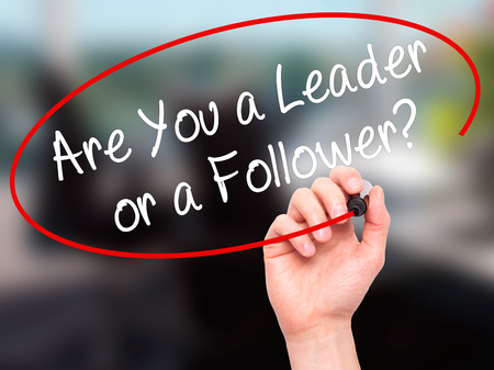 blindly: Man Hand writing Are You a Leader or a Follower? with black marker on visual screen. Isolated on office. Business, technology, internet concept. Stock Photo