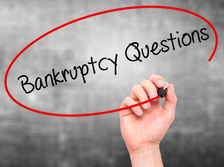 portable failure: Man Hand writing Bankruptcy Questions with black marker on visual screen. Isolated on grey. Business, technology, internet concept. Stock Photo Stock Photo