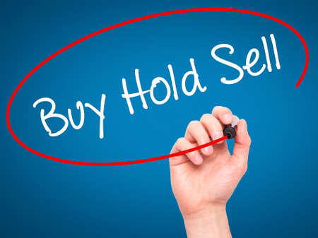 press agent: Man Hand writing  Buy Hold Sell with black marker on visual screen. Isolated on blue. Business, technology, internet concept. Stock Photo