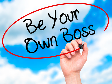 self starter: Man Hand writing Be Your Own Boss with black marker on visual screen. Isolated on sky. Business, technology, internet concept. Stock Image Stock Photo