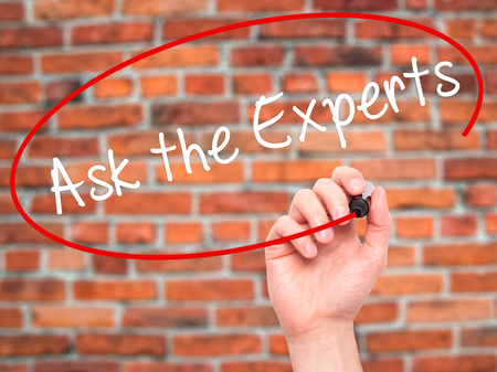 Man Hand writing Ask the Experts with black marker on visual screen. Isolated on bricks. Business, technology, internet concept. Stock Photo