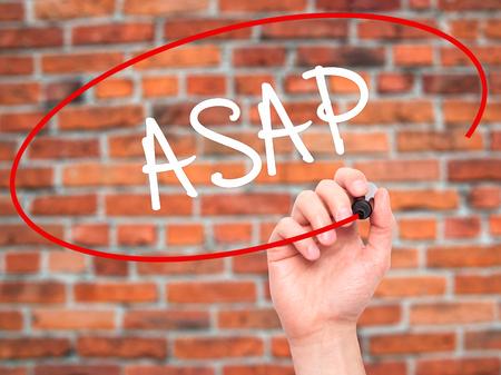 ビジュアル画面に黒のマーカーで ASAP を書く人間の手。背景に分離されました。ビジネス、技術、インターネットの概念。ストック フォト