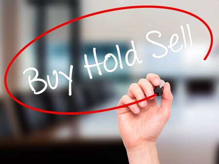 press agent: Man Hand writing  Buy Hold Sell with black marker on visual screen. Isolated on office. Business, technology, internet concept. Stock Photo