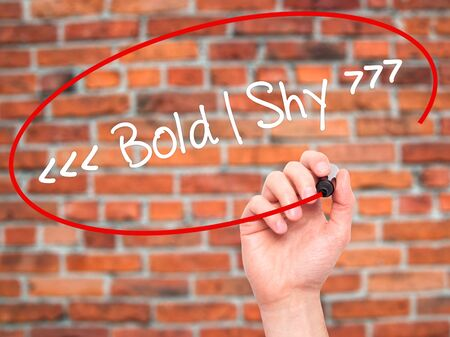 daring: Man Hand writing Bold - Shy  with black marker on visual screen. Isolated on background. Business, technology, internet concept. Stock Photo Stock Photo