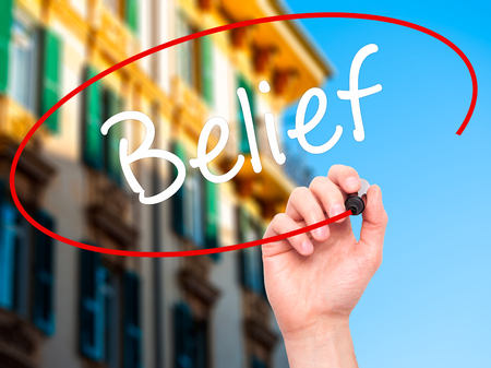 posit: Man Hand writing Belief with black marker on visual screen. Isolated on city. Business, technology, internet concept. Stock Photo Stock Photo