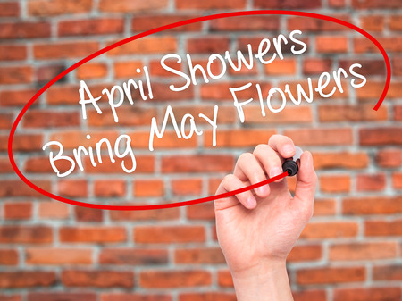 april flowers: Man Hand writing April Showers Bring May Flowers with black marker on visual screen. Isolated on bricks. Business, technology, internet concept. Stock Photo